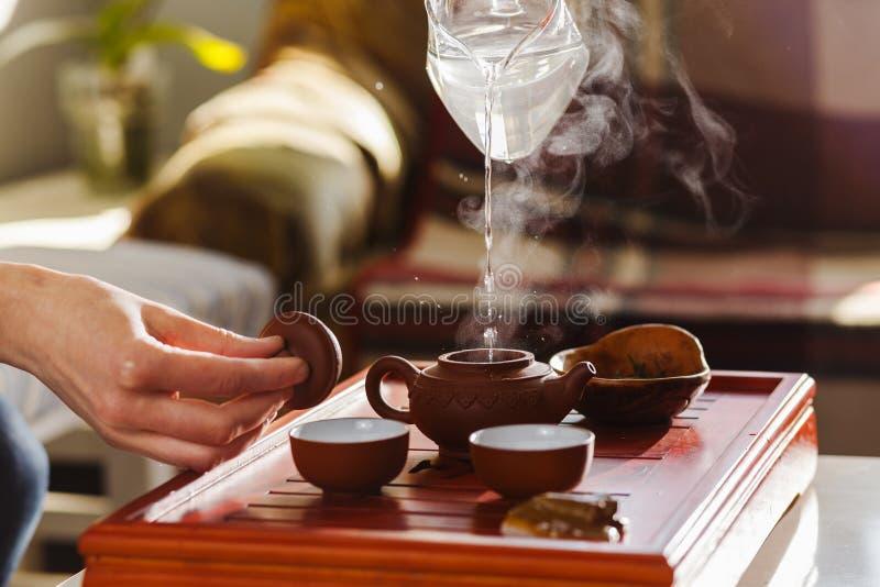 La cérémonie de thé La femme verse l'eau chaude dans la théière photo libre de droits