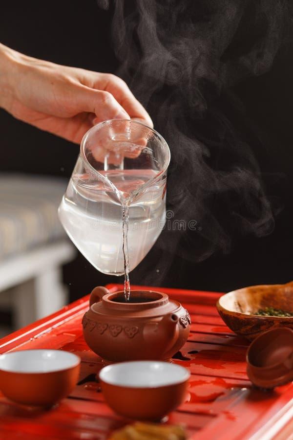 La cérémonie de thé La femme verse l'eau chaude dans la théière images libres de droits