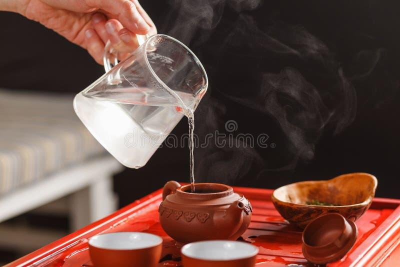 La cérémonie de thé La femme verse l'eau chaude dans la théière image stock