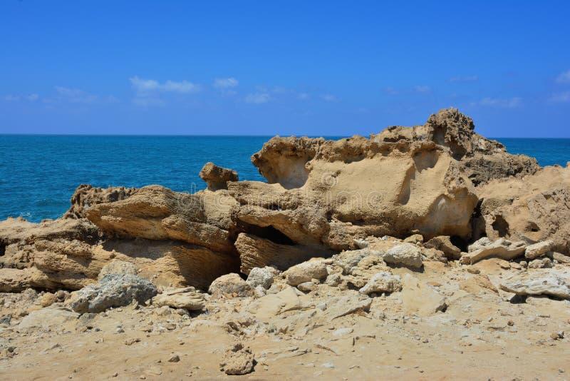 La côte pierreuse avec de grandes pierres dans la perspective du ciel bleu et de la mer image stock