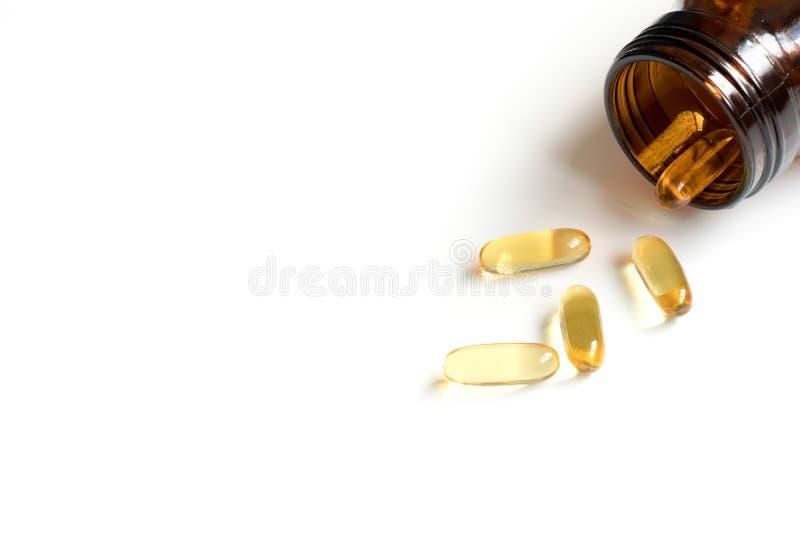 La c?psula de gelatina suave amarilla con la botella ambarina en el fondo blanco y hace que el espacio de la copia para a?ada el t fotografía de archivo
