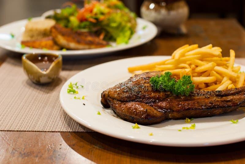 La côtelette de porc a grillé le bifteck avec des pommes frites, dessus avec le persil. image libre de droits