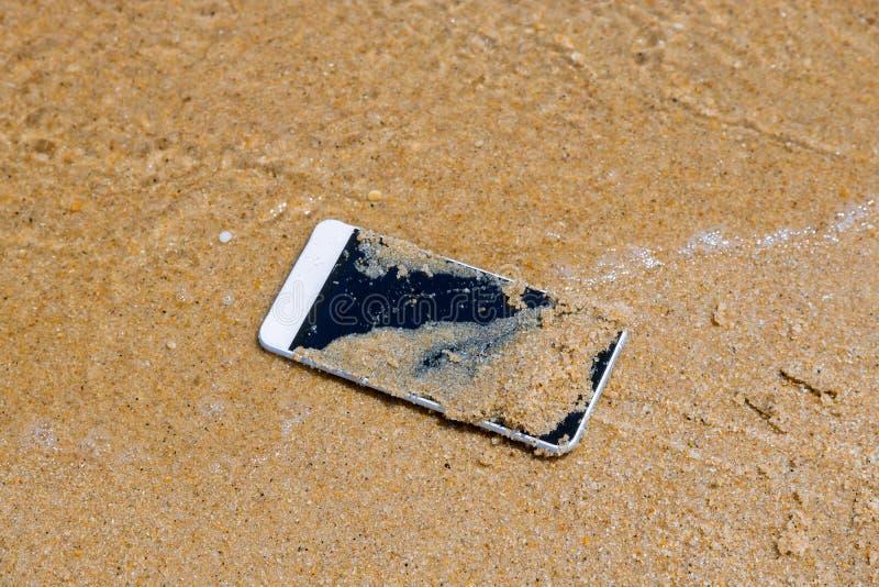 La caída del teléfono móvil a la agua de mar en la playa arenosa fotos de archivo