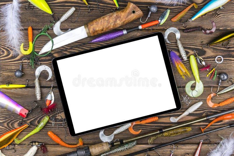 La caña de pescar, los trastos y los cebos de pesca, carrete en fondo del tablero de madera con la tableta aislaron la pantalla b fotos de archivo libres de regalías