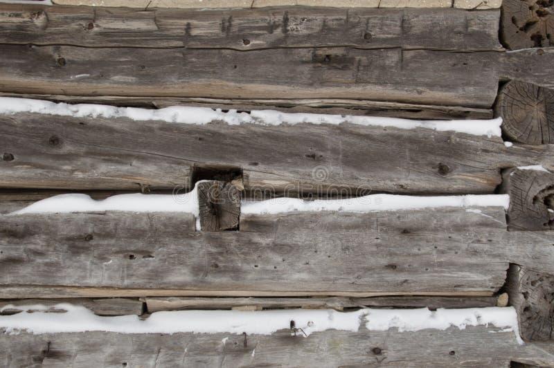 La cabaña de madera aserró registros para arrinconar el primer con nieve mientras tanto imagen de archivo libre de regalías