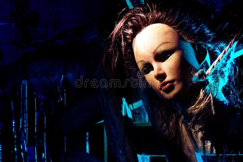 La cabeza cortada de la muñeca se ata con una cuerda a una cerca de madera Foto efectuada noche espeluznante imagen de archivo libre de regalías