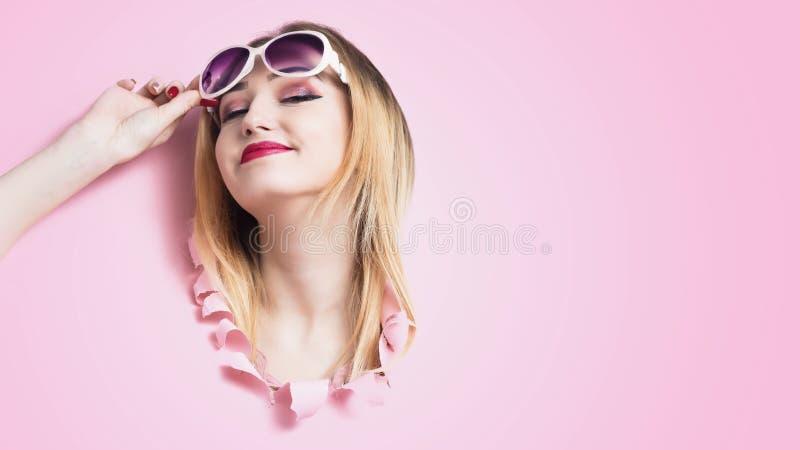 La cabeza de la muchacha en agujero de la cartulina, mujer joven levantó sus gafas de sol en el placer que miraba adelante por la fotos de archivo