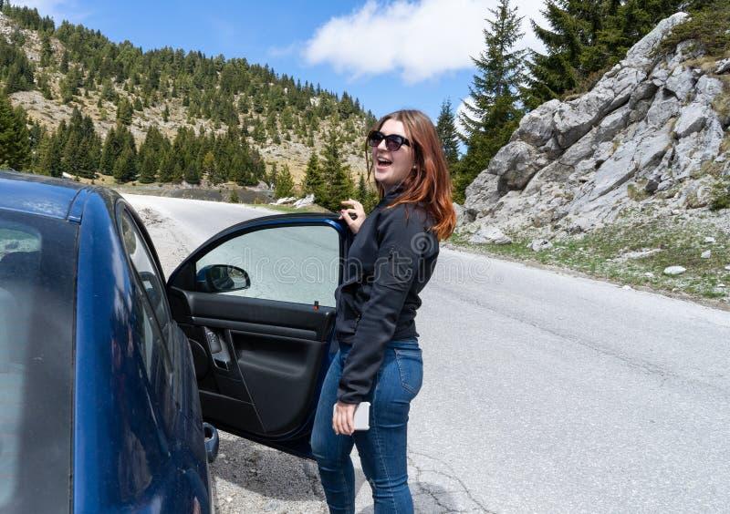 La cabeza roja feliz con los vidrios de sol entra en coche azul y teléfono elegante en la mano en un camino de la montaña fotografía de archivo libre de regalías