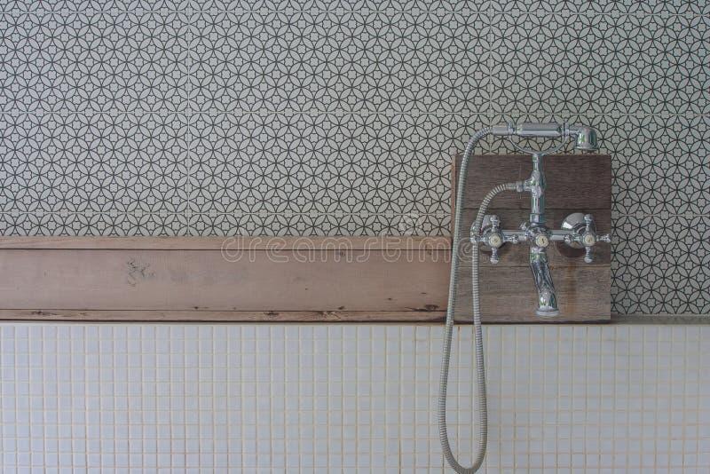 La cabezal de ducha del estilo del vintage fijó en estante de madera arriba sobre la bañera en cuarto de baño al aire libre imagenes de archivo