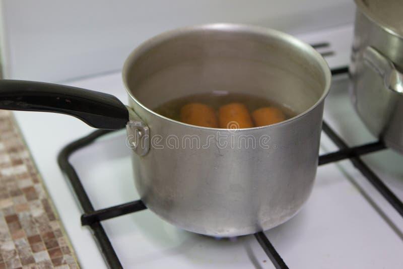 La cacerola est? en la estufa de gas con las zanahorias dentro imagenes de archivo