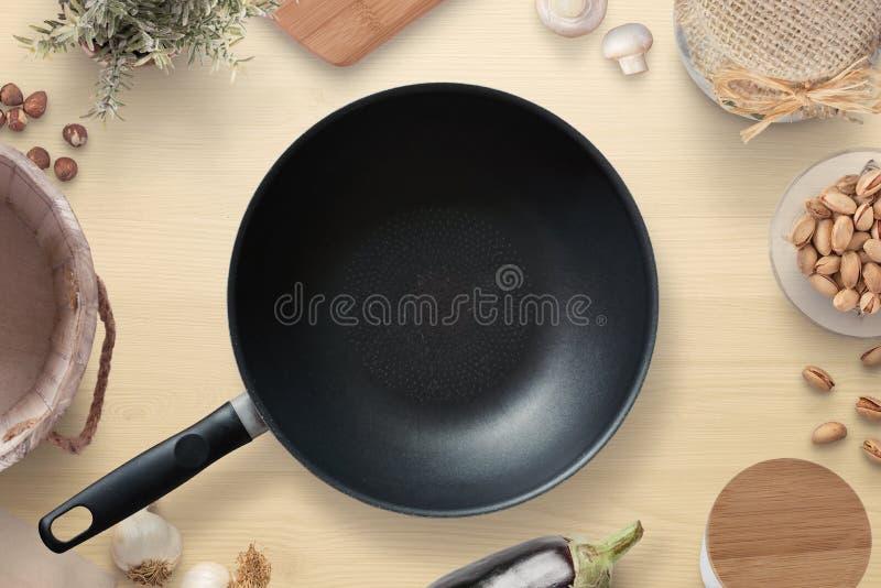 La cacerola vacía encendido kitrhen la tabla rodeada con los artículos de la cocina y los ingredientes de la comida imagenes de archivo