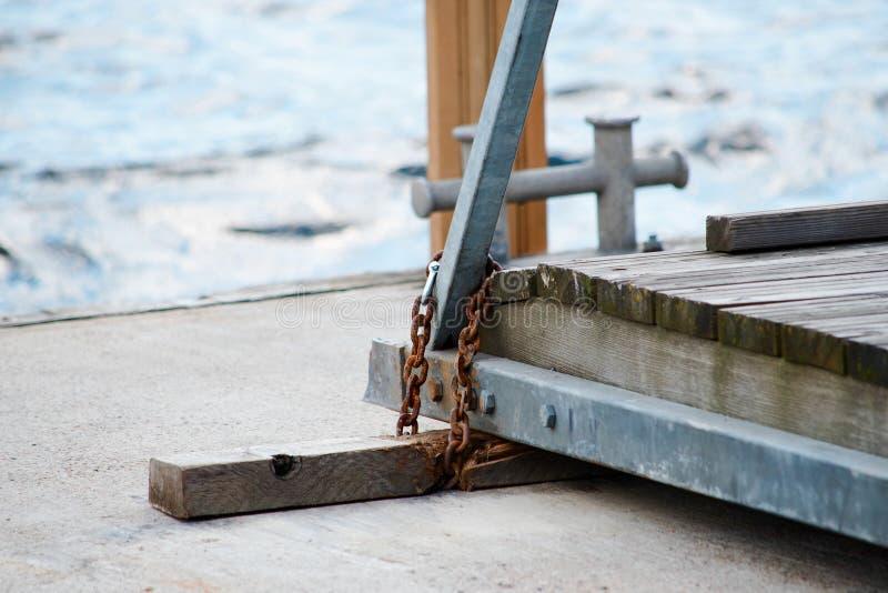 La cadena oxidada del metal sostiene un puente en el embarcadero fotografía de archivo libre de regalías