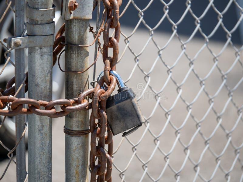 La cadena robusta envuelve una cerca de la alambrada, cerrada con un candado imagen de archivo libre de regalías