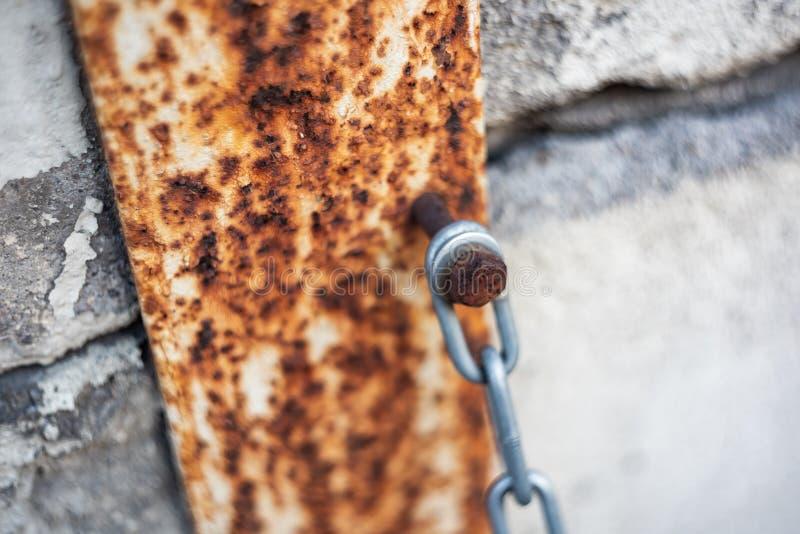 La cadena se ata a la pared con un perno oxidado fotografía de archivo