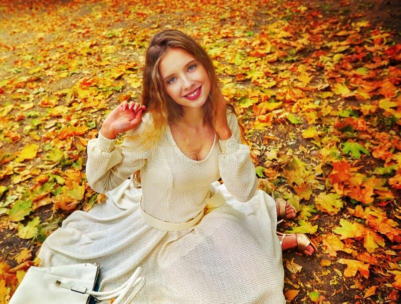 La caduta di seduta della donna del vestito da modo di autunno lascia il parco della città all'aperto fotografie stock libere da diritti