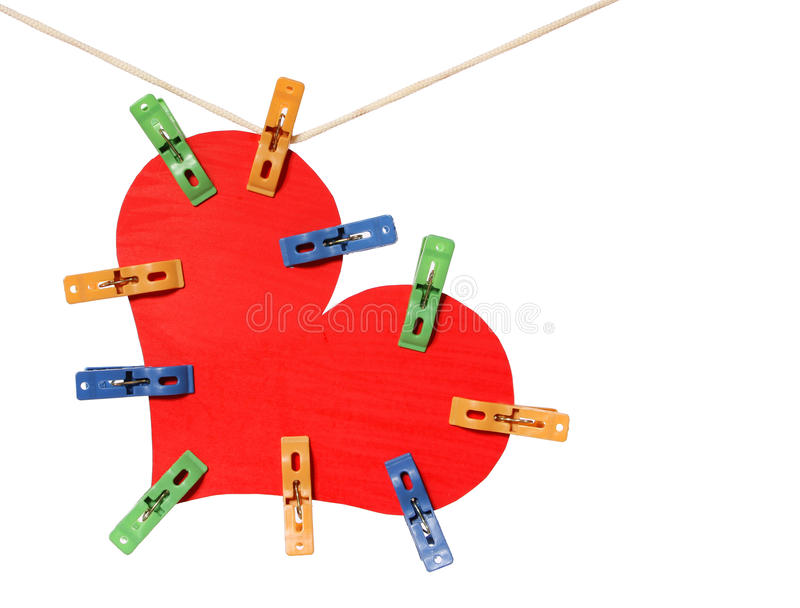 Caduta rossa del cuore sui clothespins variopinti, isolati su bianco fotografia stock