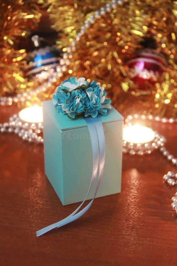La caja azul del Año Nuevo con un regalo en un fondo festivo de la Navidad fotografía de archivo libre de regalías