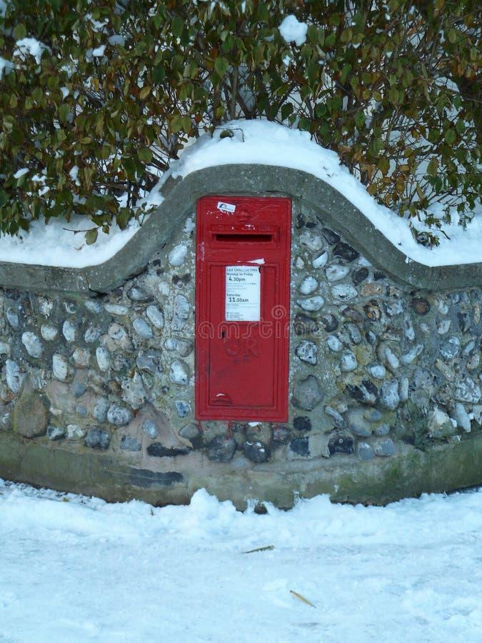 La caja BRITÁNICA roja de los posts del vintage fijó en la pared de piedra en la nieve imágenes de archivo libres de regalías