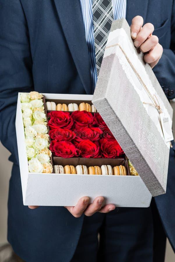 La caja con las flores y los macarrones adentro sirve las manos foto de archivo