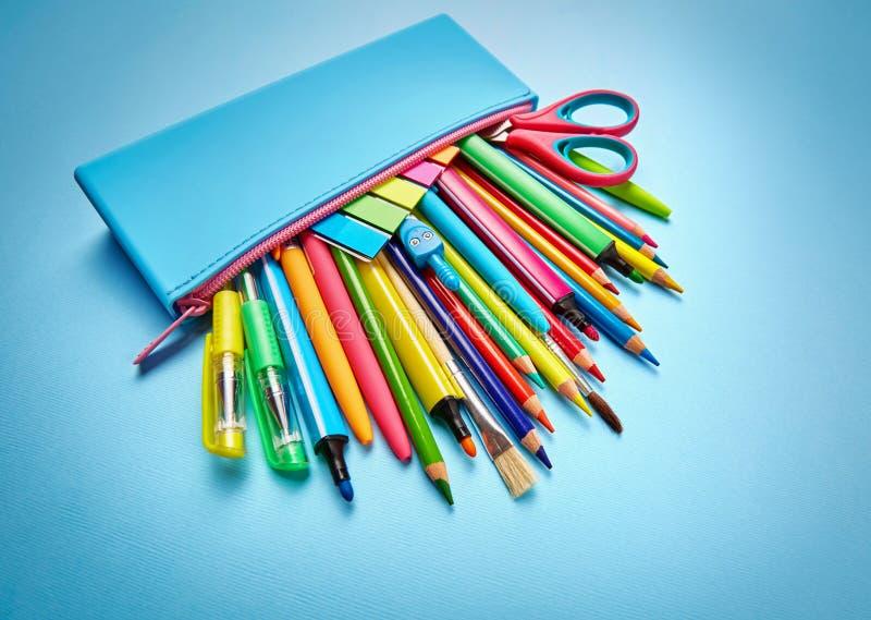 La caja de lápiz se llena de las plumas, de los lápices y de las etiquetas engomadas fotografía de archivo libre de regalías