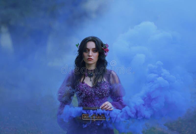La caja de Pandora la muchacha morena peligroso en un vestido lujoso sostiene un ataúd abierto en sus manos y miradas fijas atent fotografía de archivo libre de regalías