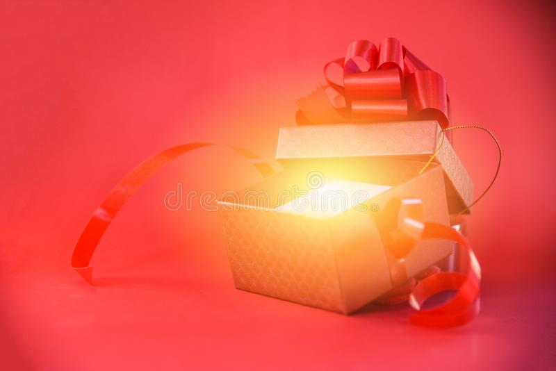 La caja de regalo abierta irradia la luz en caja roja del fondo rojo la actual con el arco rojo de la cinta por Feliz Año Nuevo d fotos de archivo libres de regalías