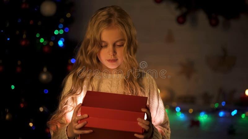La caja de regalo adorable de la abertura de la muchacha cerca del árbol de navidad, sueño infantil viene verdad foto de archivo