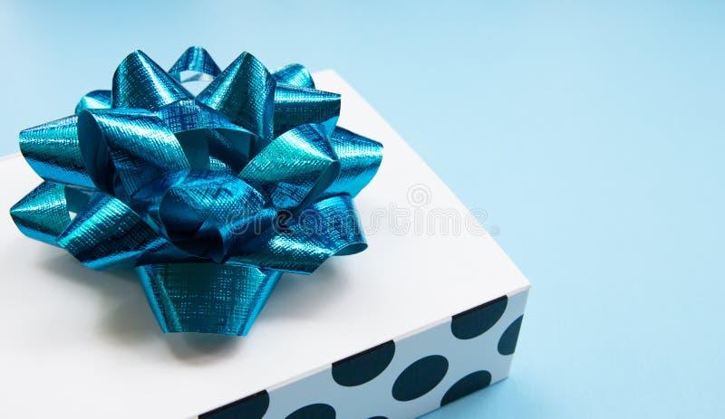 La caja de regalo blanca del lunar en un azul puso en contraste el fondo, creando una atmósfera romántica Utilizado típicamente p fotografía de archivo