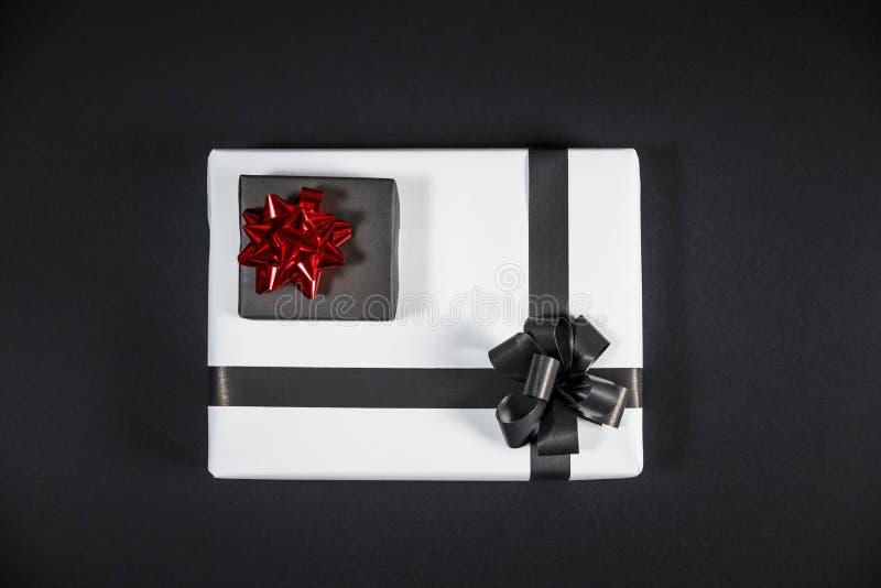 La caja de regalo blanca en una oscuridad puso en contraste el fondo, adornado con a imagenes de archivo
