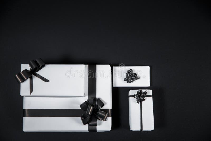 La caja de regalo blanca en una oscuridad puso en contraste el fondo, adornado con un arco texturizado, creando una atmósfera rom imagen de archivo libre de regalías