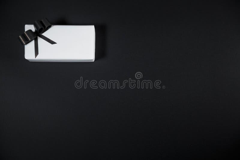 La caja de regalo blanca en una oscuridad puso en contraste el fondo, adornado con un arco texturizado, creando una atmósfera rom imágenes de archivo libres de regalías