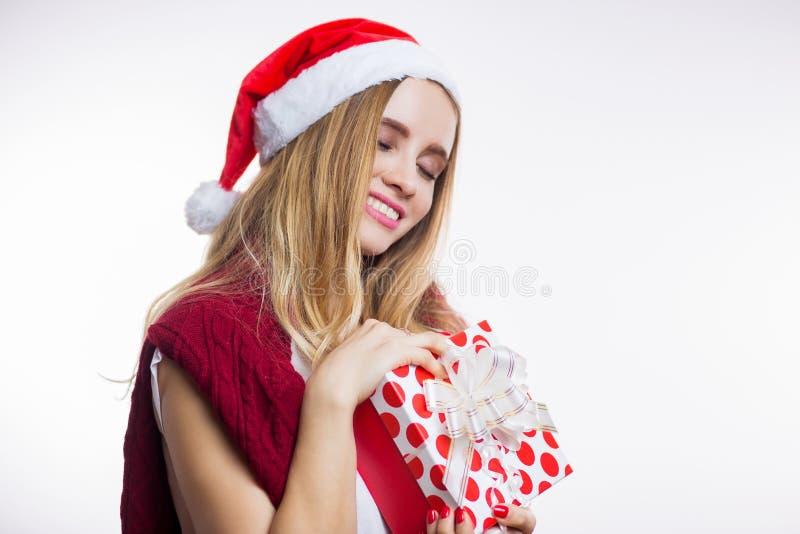 La caja de regalo bonita feliz de la tenencia de la mujer joven y se cierra feliz los ojos en un fondo blanco Expresiones faciale fotografía de archivo