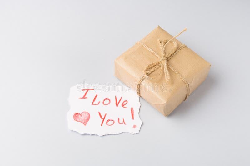 La caja de regalo con diseño del corazón imprime y te amo la tarjeta de papel en fondo gris claro fotografía de archivo