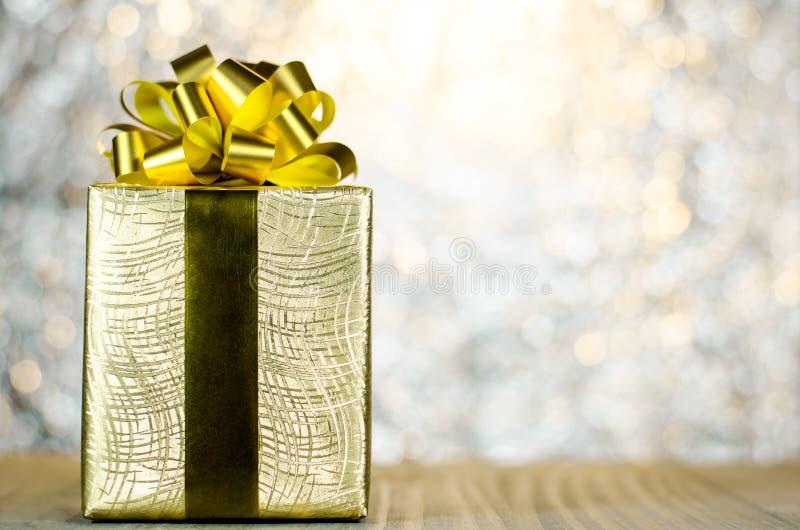 La caja de regalo de la Navidad del oro con la cinta y el arco en luces del bokeh apoyan fotos de archivo libres de regalías