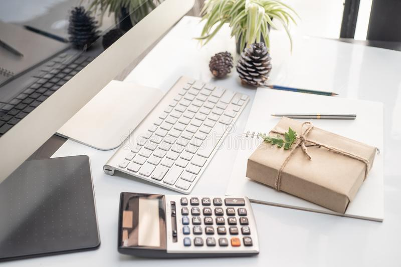 La caja de regalo envolvió el documento del arte sobre el escritorio de oficina con el ordenador del teclado, la calculadora y el imágenes de archivo libres de regalías