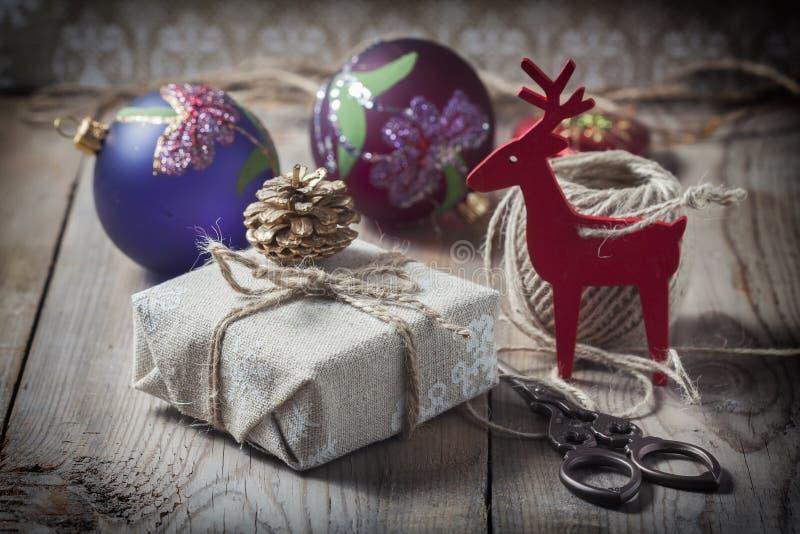 La caja de regalo envolvió el paño de lino y adornada con el cordón, yute, decoración de la Navidad en los tableros de madera del imagenes de archivo