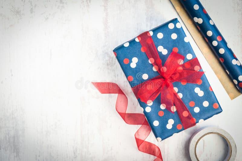 La caja de regalo envuelta en azul punteó el papel con la cinta roja en un viejo fondo de madera blanco Materiales de embalaje di imagen de archivo libre de regalías