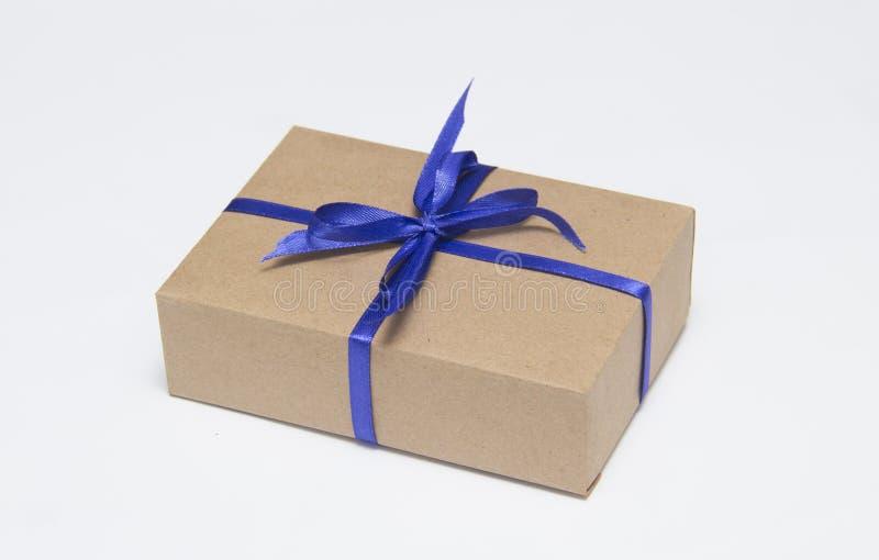 La caja de regalo de Kraft con la cinta azul est? en un fondo blanco fotos de archivo
