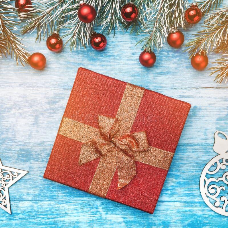 La caja de regalo de la Navidad con la cinta de oro en fondo de madera con el abeto ramifica, las chucherías rojas Composición de imagen de archivo libre de regalías
