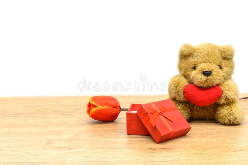 La caja de regalo roja con el tulipán y el peluche refieren la tabla de madera foto de archivo
