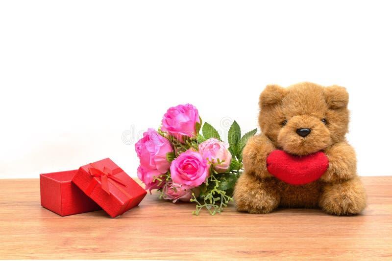 La caja de regalo roja con el tulipán y el peluche refieren la tabla de madera foto de archivo libre de regalías