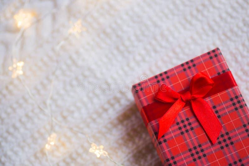 La caja de regalo roja y las luces calientes de la guirnalda en blanco hicieron punto el fondo imagenes de archivo
