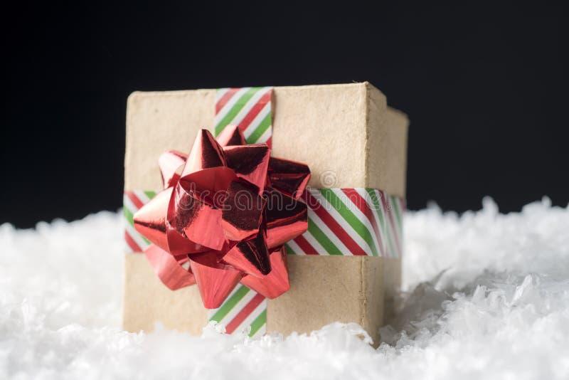 La caja de regalo de vacaciones envuelta en cinta rayada y el arco rojo brillante se sientan imágenes de archivo libres de regalías