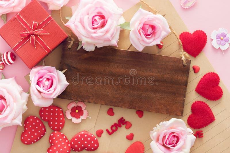 La caja de regalo de Valentine Day con los corazones rojos y las rosas tienen un marco de piso de madera para el espacio de la co imagenes de archivo