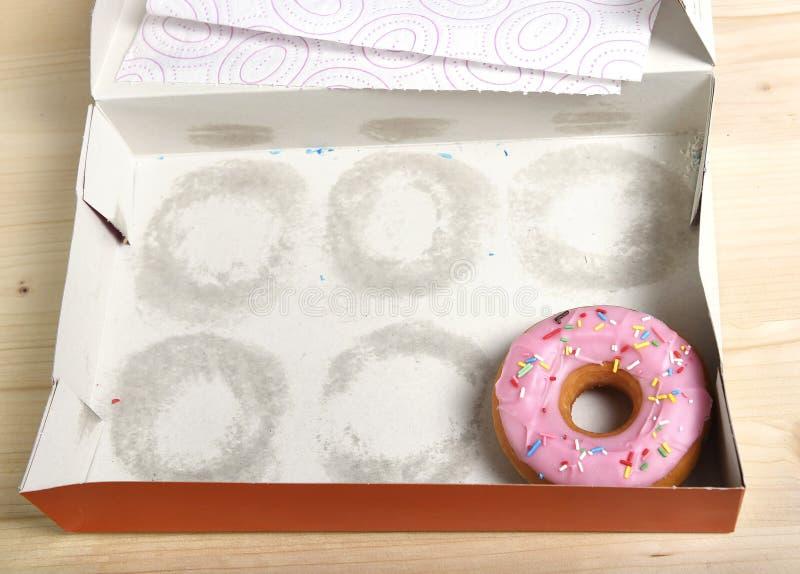 La caja de tortas vacía con el solamente un buñuelo de tentación y delicioso con los desmoches se fue fotos de archivo libres de regalías