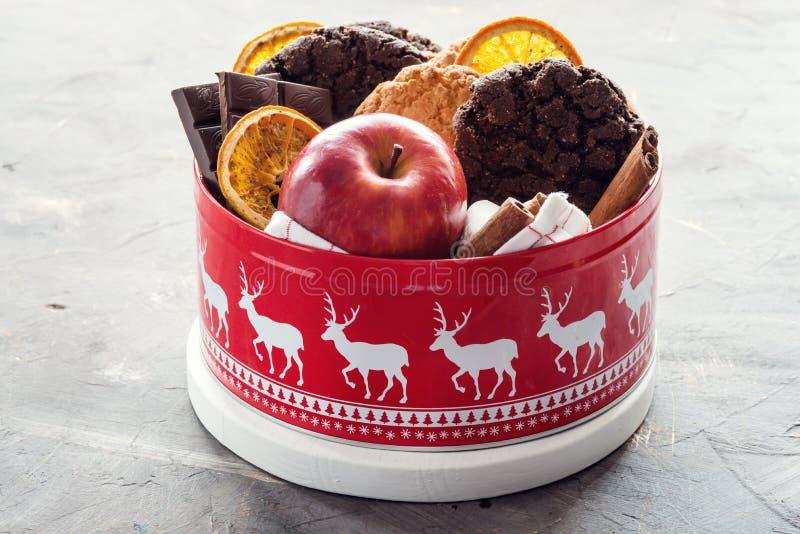La caja festiva del tarro de la Navidad con la naranja roja de las galletas de la Navidad de las barras de chocolate de la manzan fotos de archivo libres de regalías