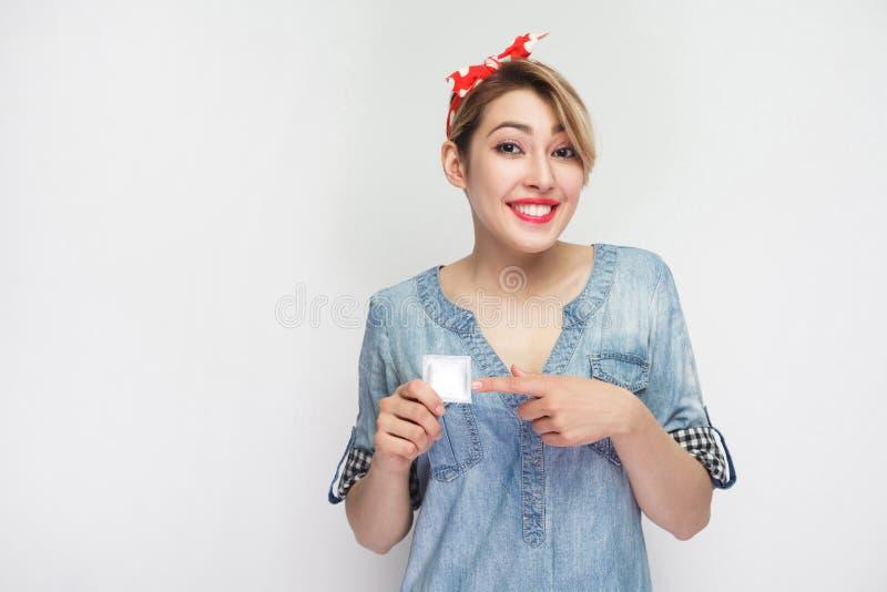 La caja fuerte protege Mujer joven hermosa feliz en la camisa casual del dril de algodón, situación roja de la venda, sosteniendo fotografía de archivo
