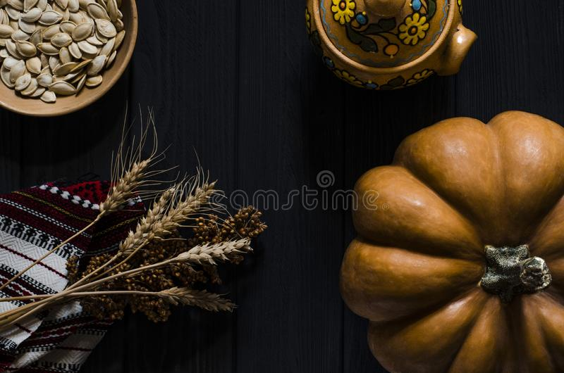 La calabaza, las semillas de calabaza y los oídos anaranjados del trigo mienten en un fondo de madera negro imagen de archivo libre de regalías