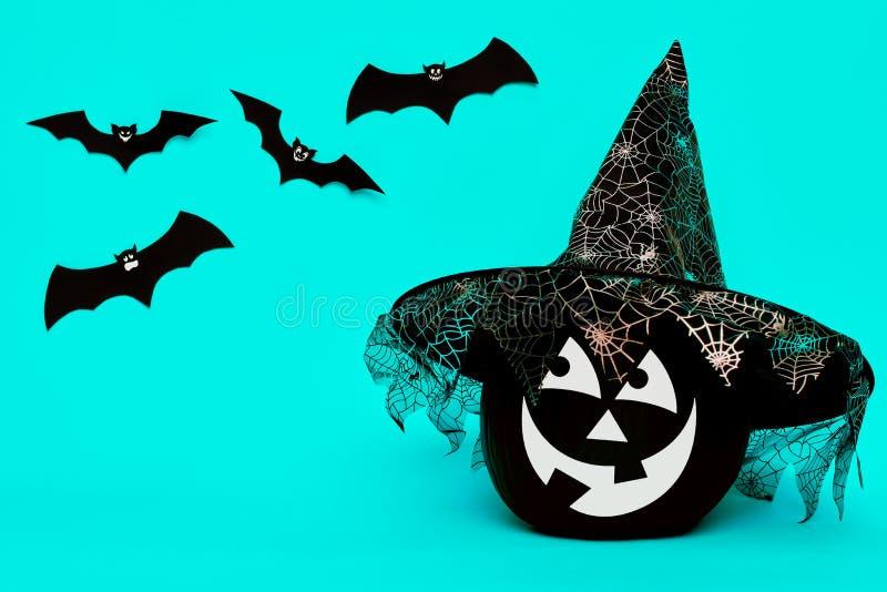 La calabaza negra grande de Halloween con el sombrero sonriente lindo de la bruja de la cara que lleva que mira el papel del vuel fotos de archivo libres de regalías