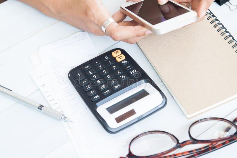 La calculadora con la cuenta se desliza en la tabla de madera con la mano de la mujer usando imágenes de archivo libres de regalías